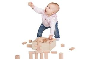 Kind spielt mit Holzbausteinen und hält Bauklotz in die Luft