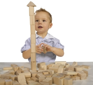 Kleinkind spielt mit Heros Holzbausteinen und Bauklötzen natur
