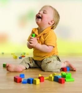 Junge spielt mit bunten Heros Bauklötzen und Holzbausteinen